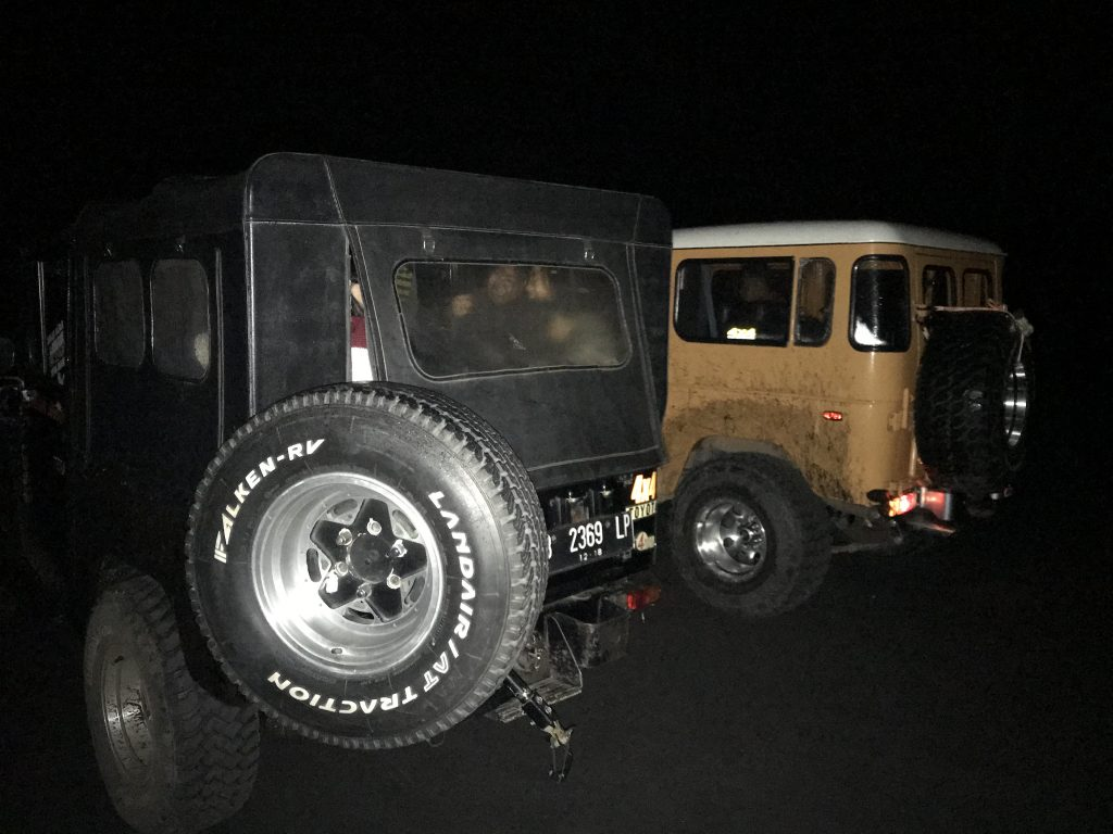 Picture of two jeeps in the dark